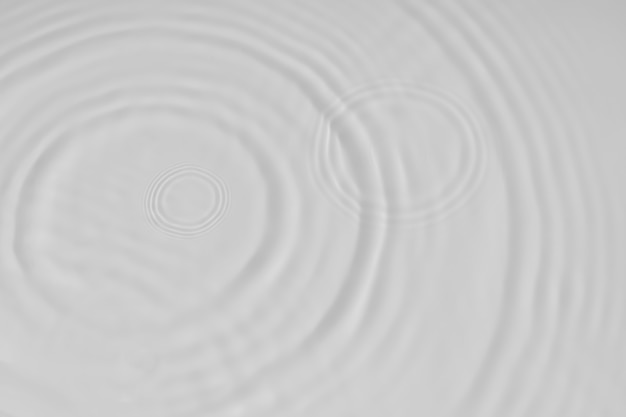 液体の白い表面上の水の静かな波紋の背景の水のテクスチャの円と泡