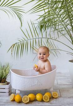 テキストのための場所と白い背景の上のレモンと白いお風呂で水処理女の赤ちゃん