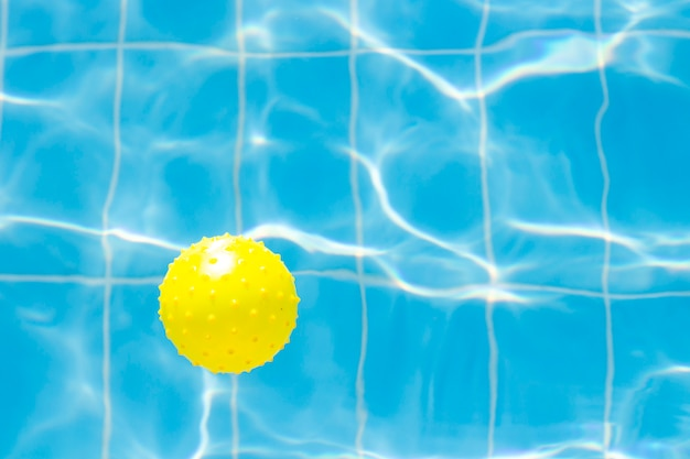 Water vibrations in the swimming pool with sun reflection and a yellow ball for playing. blue swimming pool surface, water in swimming pool. flat lay, top view