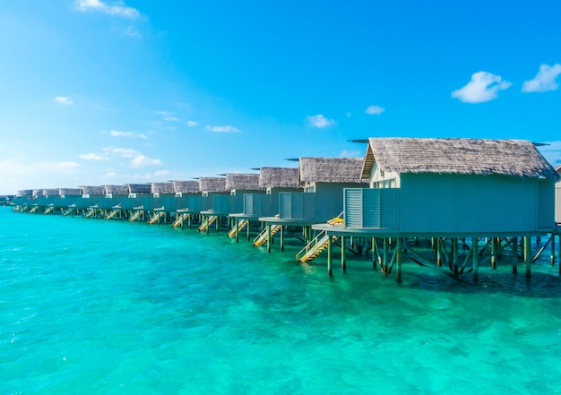 Water villas over calm sea  in tropical maldives island .
