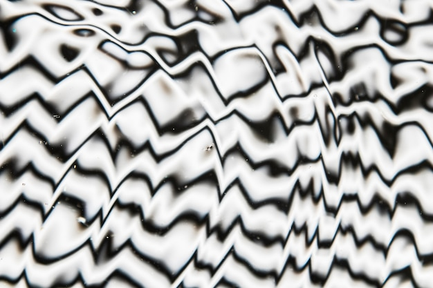 Water waves on a black and white pool surface