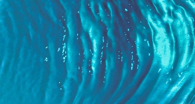 ターコイズブルーの背景に泡と水の波の上面図。水面テクスチャ