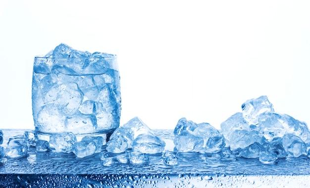 白い背景で隔離のガラスの砕いた氷で水します。