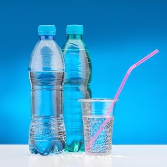 Вода с газом в пластиковом стакане с розовой соломкой. бутылка с пресной водой.