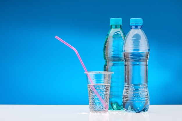 Water with gas in plastic glass with pink straw. bottle with fresh water on white table and blue background.