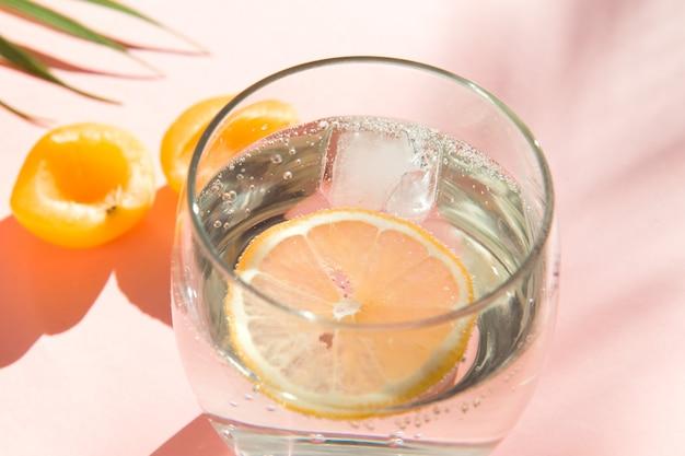 Вода со льдом и лимоном прохладно летние напитки здоровая еда фрукты и стакан содовой на розовом цветном фоне
