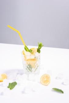 흰색 배경에 얼음과 레몬 여름 최소한의 정물이 있는 물.