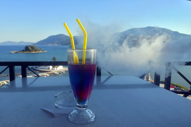 Water with ice and colorful syrups it is on table with a panoramic view of sea and smoke backgound