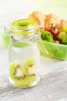 Water with kiwi and green lunch box