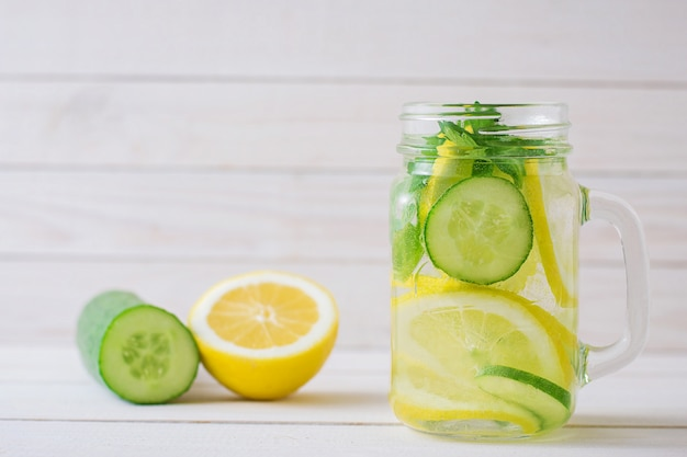Water with lemon and cucumber in a glass cup