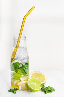 Вода с лимоном и мятой, лаймом и льдом со стеклянной безотходной трубочкой