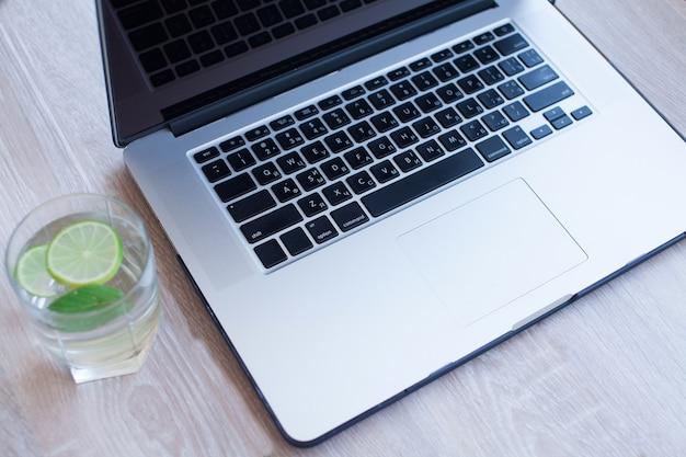 Вода с лимоном возле ноутбука.