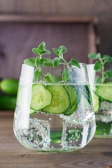 キュウリ、氷、ミントの葉が付いている水は、木製のテーブルの透明なガラスに残します