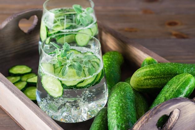きゅうり、氷、ミントの葉が付いている水は、テーブルの上の木製トレイに透明なガラスと野菜の葉します。