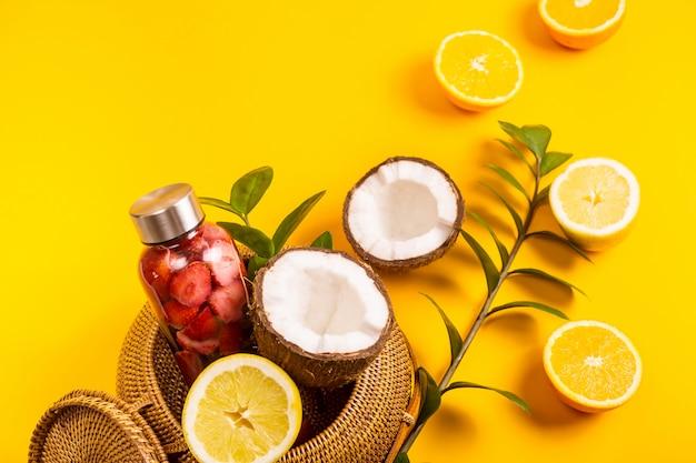 Вода с клубникой, апельсинами, лимонами и кокосами на желтом с соломенной сумкой