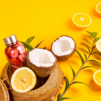 Water with strawberries, oranges, lemons and coconuts on yellow with a straw bag