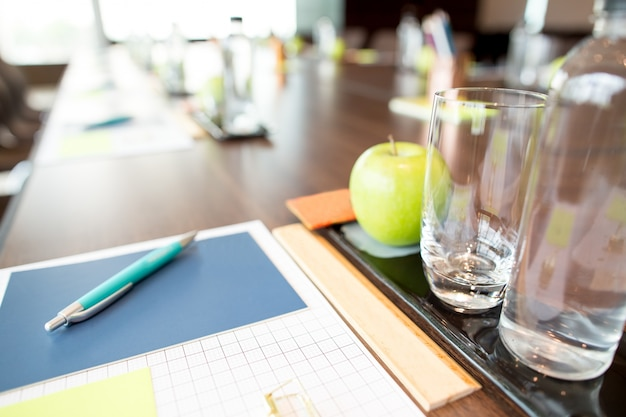 Water and writing utensils on conference table