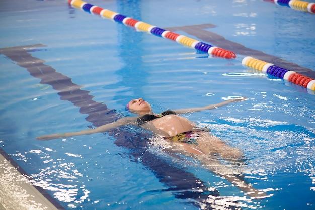 Водная йога, беременная женщина делает упражнения йоги в бассейне