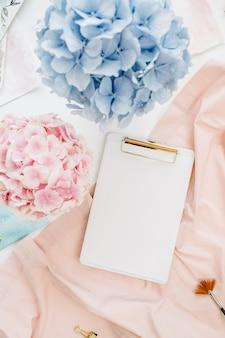 コピースペースクリップボード、パステルアジサイの花の花束、水彩画、桃色の毛布と水彩画家のホームオフィスデスクワークスペース