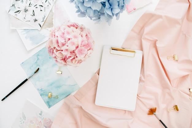 복사 공간 클립 보드, 파스텔 수국 꽃 꽃다발, 수채화 그림, 복숭아 담요와 수채화 작가 홈 오피스 책상 작업 공간
