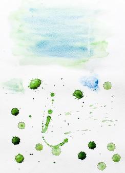 紙の上の青と緑の色の水彩のしみと水しぶき