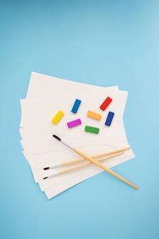 さまざまなサイズの水彩ブラシは、青い背景に水彩紙とさまざまな色と一緒に横たわっています。描画レッスン。クローズアップ、上面図。