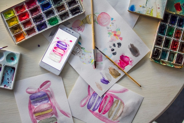 Watercolor drawings on the table with paints close-up