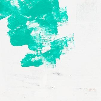 白い表面に水彩の緑色のブラシストロークの背景