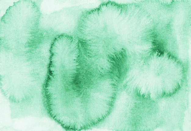 Акварельные зеленые пятна на фоне белой бумаги. ручной росписью