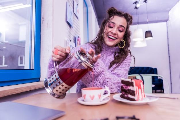 水彩の心。テーブルに座ってかわいいカップに温かいお茶を注ぐポジティブな女性を笑う
