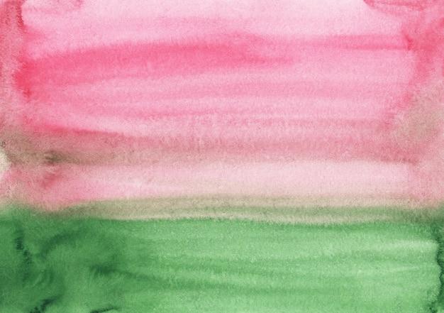 水彩の淡いピンクと緑の抽象的な背景のテクスチャです。紙にブラシストローク。