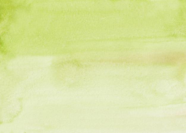 水彩の淡い黄緑色の背景テクスチャ。手描きのライムオーバーレイウォーターカラー。紙の汚れ。