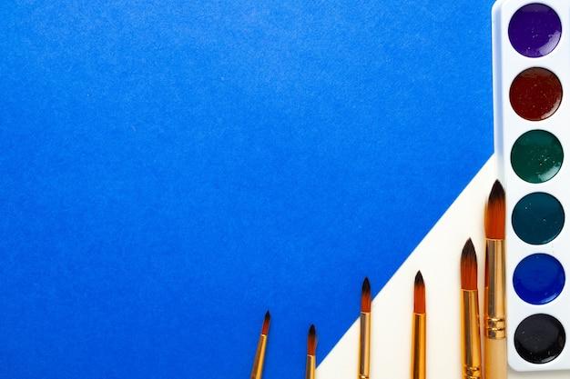 수채화 물감 페인트 상자와 파란색과 흰색 배경 평면도에 브러쉬 세트
