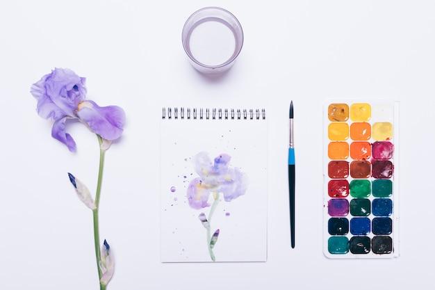 水彩絵の具、ブラシ、青い花、パターン、白い背景の上の水でガラス
