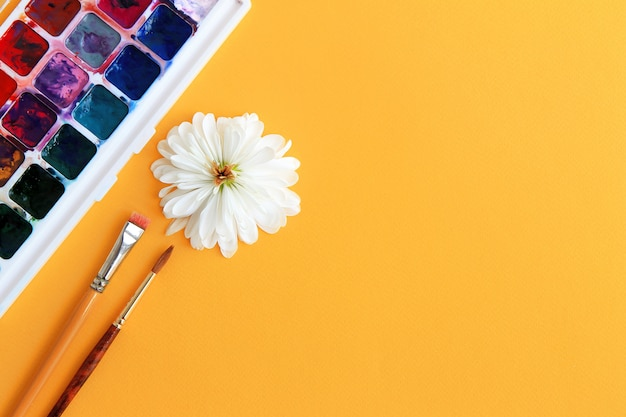 Watercolor paint, brushes and flower with white petals on a yellow background concept of creativity
