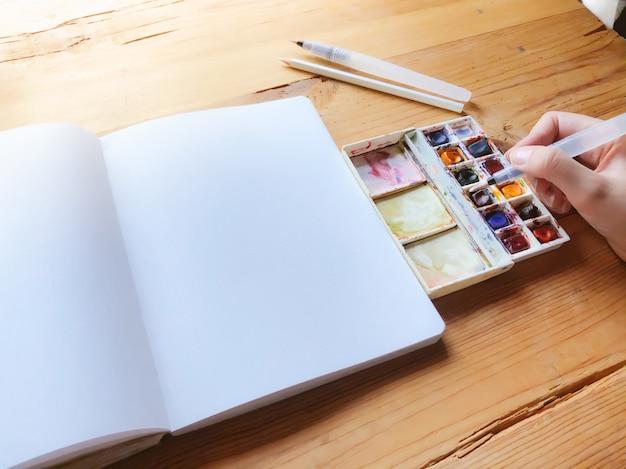 새로운 그림을 만드는 데 사용되는 수채화 물감 캔버스와 브러시. 손을 잡고 브러쉬입니다. 도트 노트에서 글 머리 기호 시작. 새로운 시작. 예술과 창의성 개념.