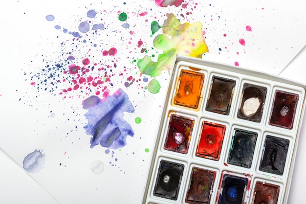 Watercolor paint set with swatches of paint splatter on paper