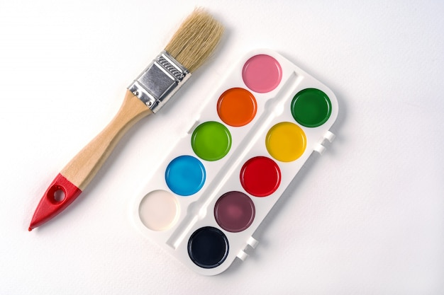Watercolor paint in white box and brush, isolated