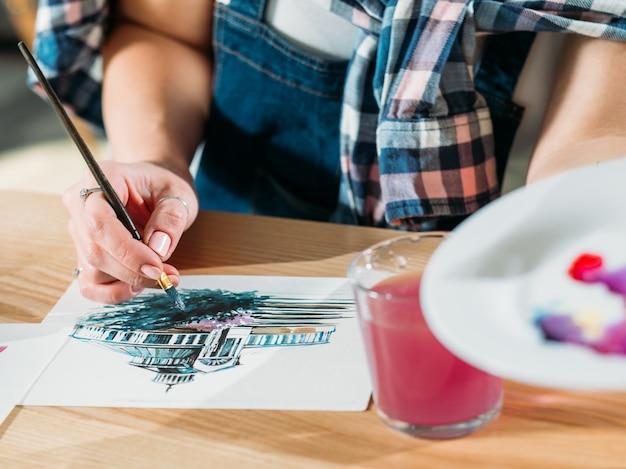 水彩画。仕事中のアーティスト。カラーミックスブラシストロークを行う画家。