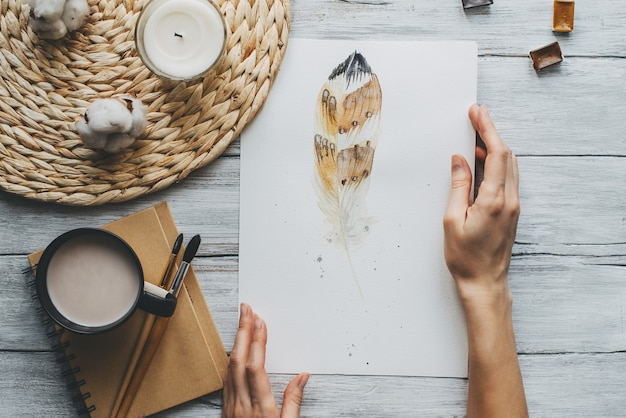 Watercolor painting with paintbrush and mug of coffee on wooden texture.