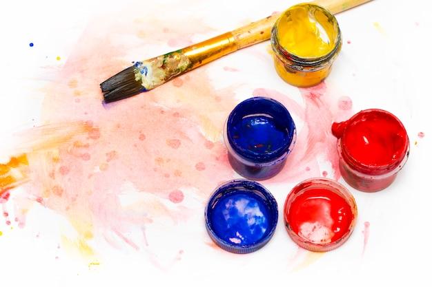 水彩絵の具、アートブラシ、描画用の白い紙。上からの眺め。