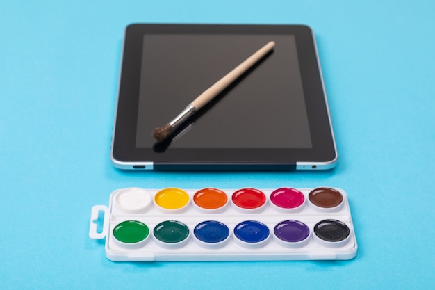 Watercolor paints and brush lying on tablet isolated on blue background