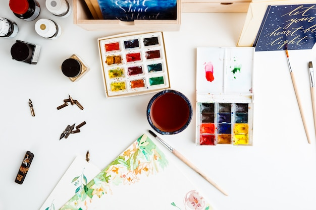 Watercolor paints brushes art details over white wall
