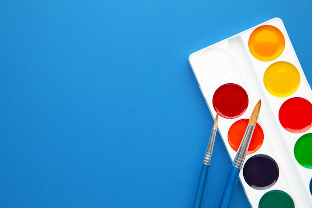Watercolor paints and brushes on blue. creative artistic mockup with copyspace.