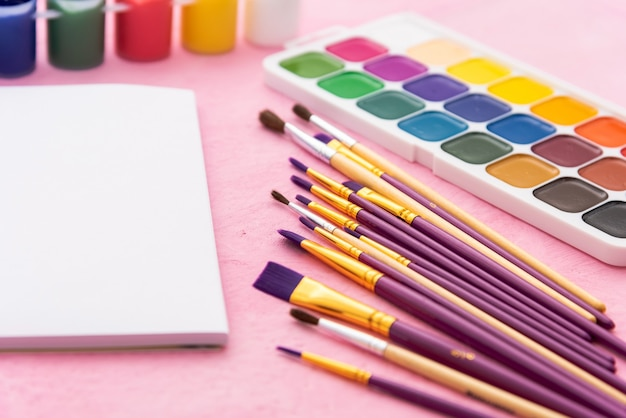 Watercolor paints and brushes for drawing on a pink table. copy space.