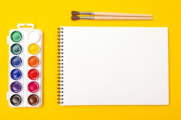 Watercolor paints and brushes with album for drawing isolated on yellow background