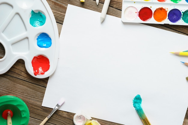 Watercolor paints and brushes with blank white paper on wooden table