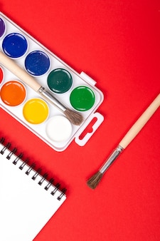Watercolor paints and brushes with drawing album isolated on red background top view