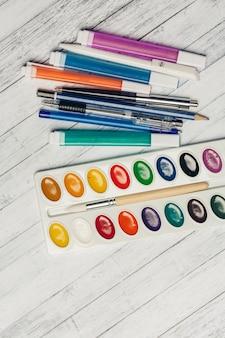 木製のテーブルトップビューに水彩絵の具色鉛筆とマーカー