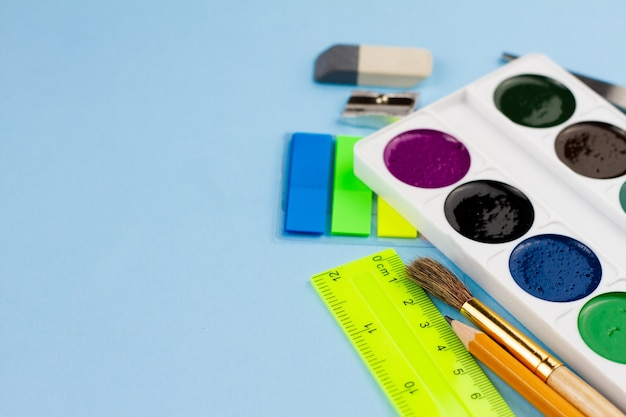Watercolor paints lie on the stationery on a blue background.